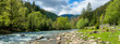 Leinwandbild Motiv river in mountains. wonderful springtime scenery of carpathian countryside. blue green water among forest and rocky shore. wooden fence on the river bank. sunny day with clouds on the sky