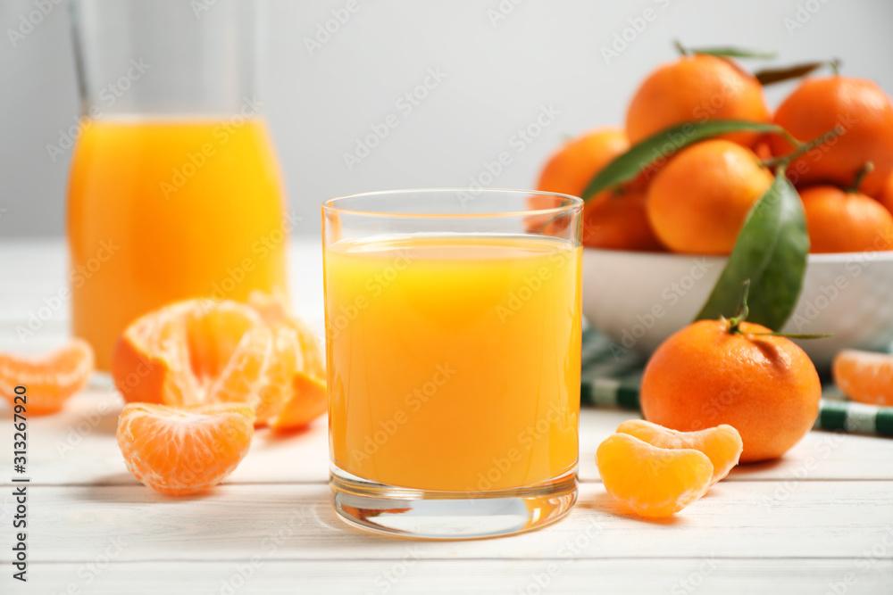 Fototapeta Glass of fresh tangerine juice and fruits on white wooden table