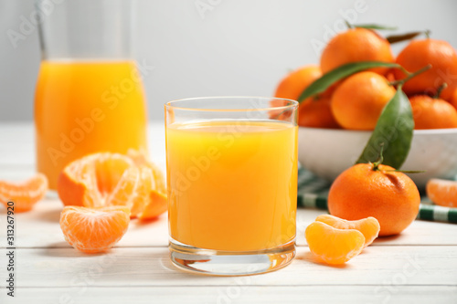 Obraz Glass of fresh tangerine juice and fruits on white wooden table - fototapety do salonu
