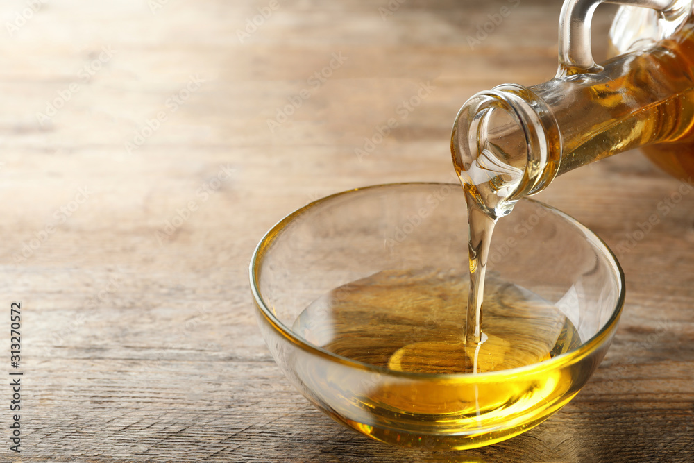 Fototapeta Pouring cooking oil from jug into bowl on wooden table