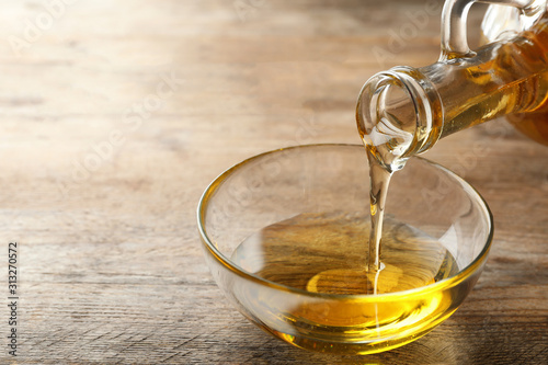 Pouring cooking oil from jug into bowl on wooden table
