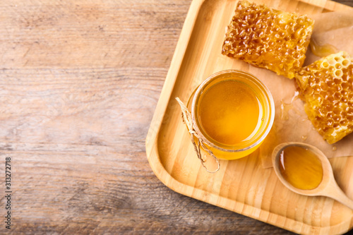 Fotografía  Tasty aromatic honey on wooden table, flat lay. Space for text