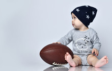 Little Baby Boy Toddler In Grey Casual Jumpsuit, Black Cap With Stars And Barefoot Sitting On Floor With Rugby Ball