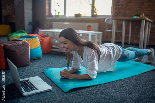 Positive active young woman working out at home Fototapet