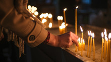 Adult Caucasian Light Candle In Orthodox Church