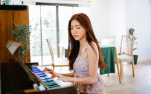 Beautiful Young Asian Woman Playing Piano In Living Room At Home.  Enjoy Her Free Time, People Relaxing Time With Instrument. Lazy Day Off Concept.