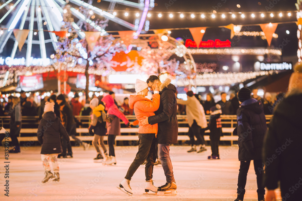 Fototapeta Beautiful couple have fun in ice arena. active date ice skating on ice arena in evening city square in winter Christmas Eve. St. Valentine's Day at the city ice rink. New Year's holidays in city Kiev
