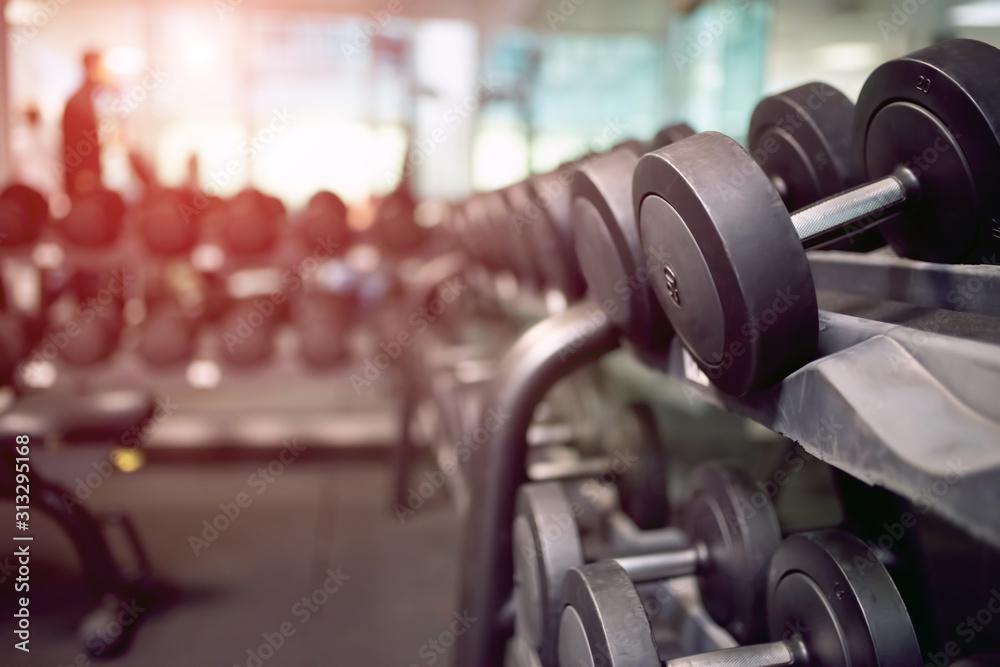 Fototapeta Dumbbells in a gym, flare effect