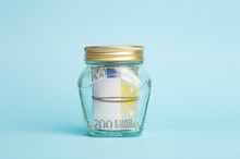 Money Euro Deposit Concept. Euro Cash In A Glass Jar On A Blue Background. Cash Operations, Business And Banking Concept