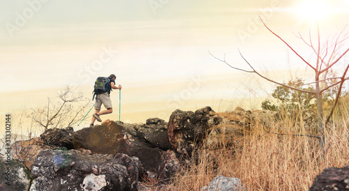 Obraz Rear view of tourist guide on trekking path with poles and backpack walking on rock to the peak. Landscape trail travel concept. - fototapety do salonu