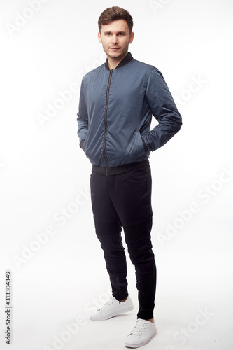 Fototapeta Young european man in white sweater and black pants, blue bomber jacket posing on white background