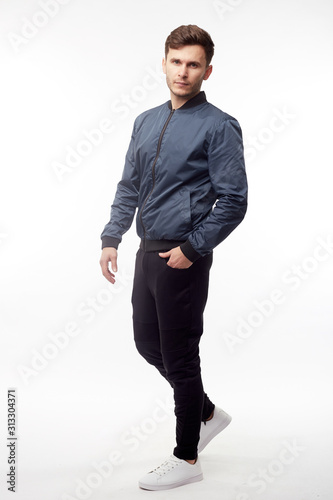 Papel de parede Young european man in white sweater and black pants, blue bomber jacket posing on white background