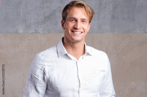 Fototapeta young positive guy in a business white shirt without a tie, looking at the camer