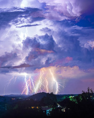 Thunder storm and lightning over hills and city