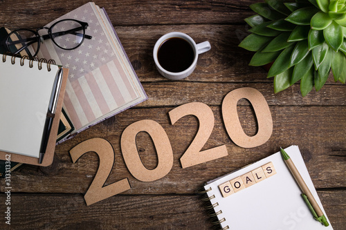 Obraz Office desk table with notebooks, coffee cup. New year 2020 resolutions or goals list. Goal, plan, strategy, politics, international relations, economics concept - fototapety do salonu