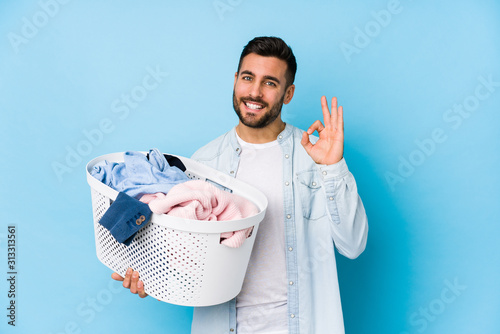 Obraz na plátně Young handsome man doing laundry isolated cheerful and confident showing ok gesture