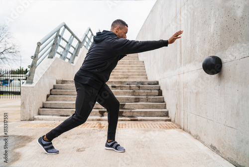Fototapeta Athletic man doing wall ball exercise. obraz
