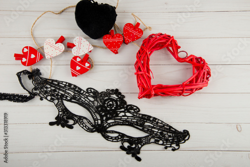 Top view on different romantic hearts and lace face mask on white wooden table