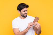 Young Handsome Man With Beard Over Isolated Yellow Background Taking A Chocolate Tablet And Happy
