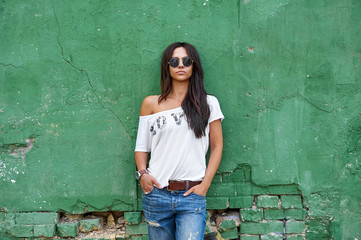Outdoor street portrait of stylish woman in sunglasses and casual clothes