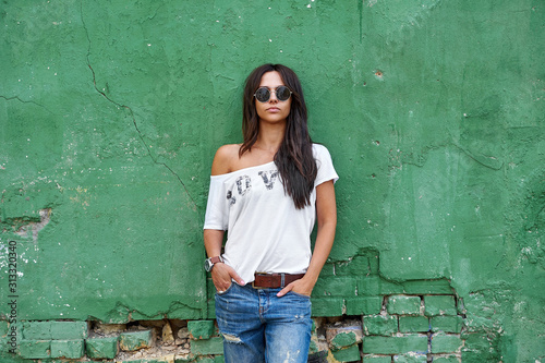 fototapeta na lodówkę Outdoor street portrait of stylish woman in sunglasses and casual clothes