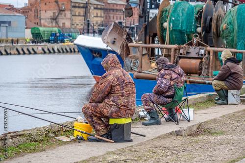 Valokuva  Fishermen catch smelt in the port in winter.