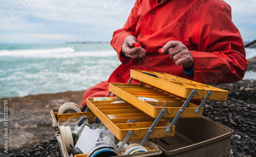Fotomural  Fisherman with fishing equipment box.