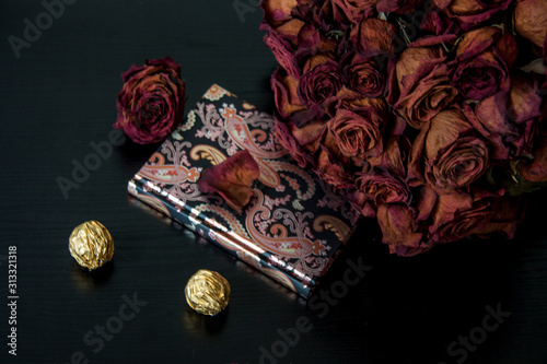 Romantic vintage composition on dark background. Red dry rose flowers and notebook. Background for invitation, happy birthday, valentines day greetings. For banner and postcard with place for text.
