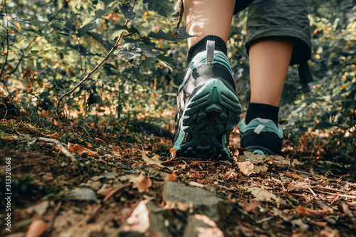 Fototapeta Muddy boots of hiker on forest trail. Traveler feet are stepping on the ground with fallen leaves. Close up of the sole of dirty shoes. Adventure and hiking concept outdoor. Hipster lifestyle obraz