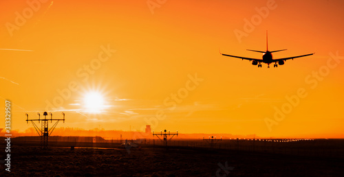 Back view silhouette of airplane landing at the airport at sunny orange and purple sunset Canvas Print
