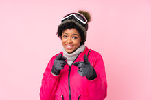 African American Skier Woman With Snowboarding Glasses Over Isolated Pink Background Points Finger At You