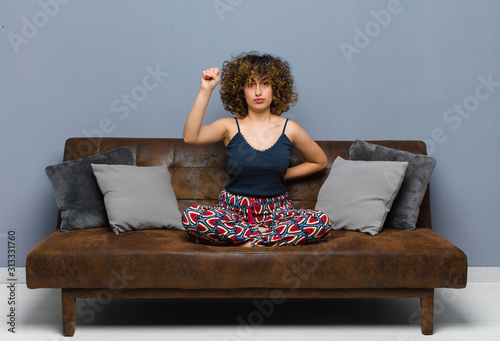 Photo young pretty woman feeling serious, strong and rebellious, raising fist up, protesting or fighting for revolution sitting on a sofa