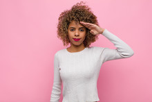 Young African American Woman Greeting The Camera With A Military Salute In An Act Of Honor And Patriotism, Showing Respect Against Pink Wall