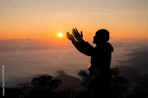 Slika na platnu Silhouette of christian man hand praying,spirituality and religion,man praying to god