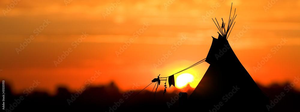 Fototapeta An American Indian tipi (teepee) against an evening sunset.