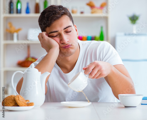 Photo Man falling asleep during his breakfast after overtime work