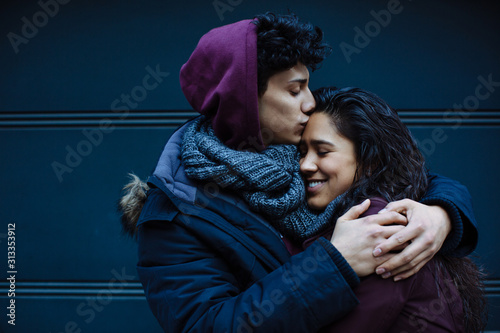 Close up portrait of a happy young hispanic couple embracing each other and kiss Canvas Print