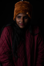 Portrait Of An Young And Attractive Dark Skinned Indian Woman Wearing Woolen Cap And Jacket Feeling Cold In A  Winter Night In Dark Background. Winter And Christmas