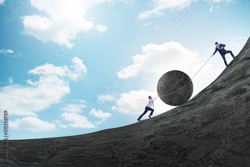 Teamwork example with business people pushing stone to top Fototapeta