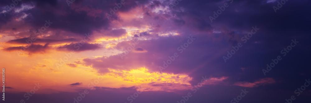 Fototapeta Beautiful sunset sky above clouds with dramatic light. Panorama banner format