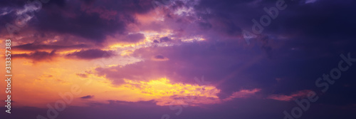 Beautiful sunset sky above clouds with dramatic light. Panorama banner format