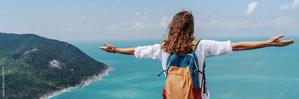 Fototapeta Girl relaxing on tropical hill top with arms open felling freedom witn beautiful ocean view from top. Freedom and happiness concept.