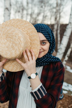 Portrait Of Young Woman Wearing Hijab And Covering Half Of Her Face With Hat.