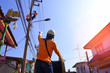 Focus on foreground and low angle view of electricians team are working to install electrical systems on electric power poles with flare light and blue sky background at morning time