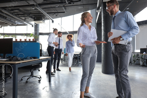 Cuadros en Lienzo Group of modern business people are talking and smiling while standing in the of