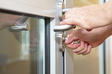 Hands Opening Locked Door  With Typical Key  - Close Up