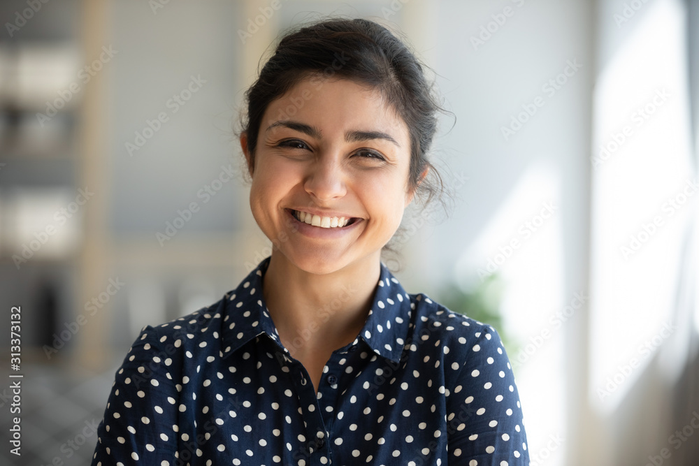 Fototapeta Cheerful indian girl standing at home office looking at camera