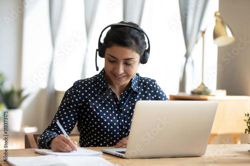 Indian girl student wear headset study online teacher write notes