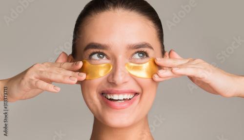 Tablou Canvas Pretty girl applying golden collagen patches under her eyes