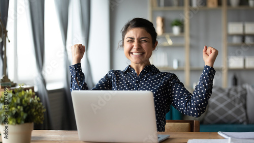 Euphoric young indian girl celebrate online victory triumph with laptop Wallpaper Mural